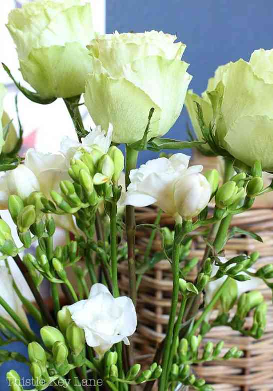 Freesia and roses in a simple glass pitcher.