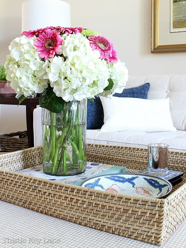 Style an ottoman with a woven tray and flowers.