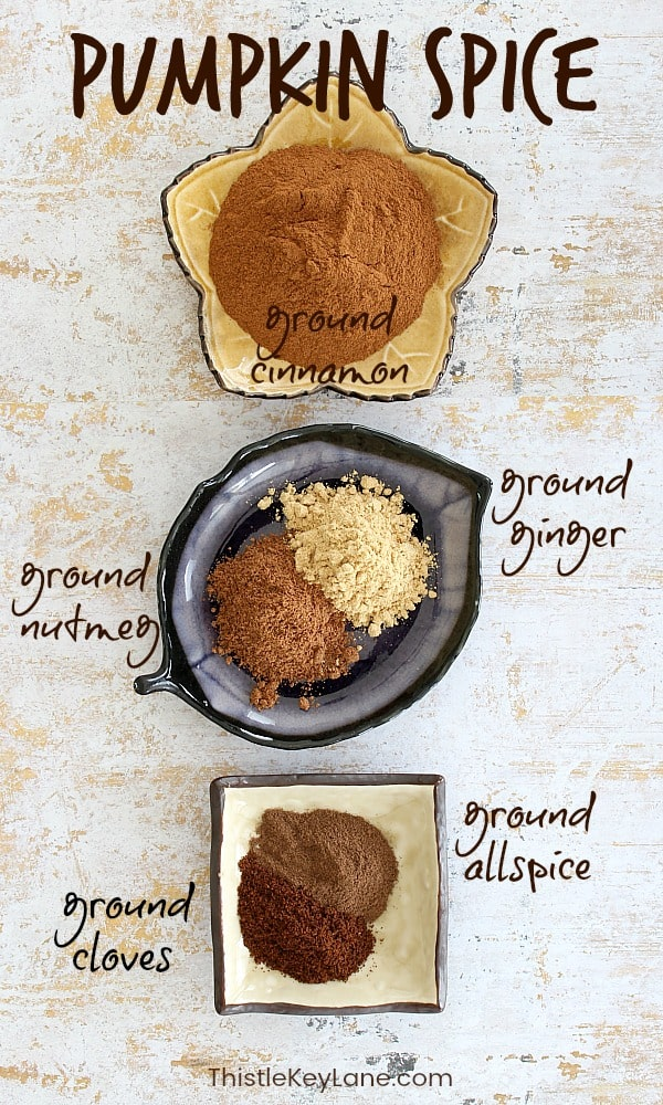 Spices cinnamon, ginger, nutmeg, cloves and allspice in open dishes.