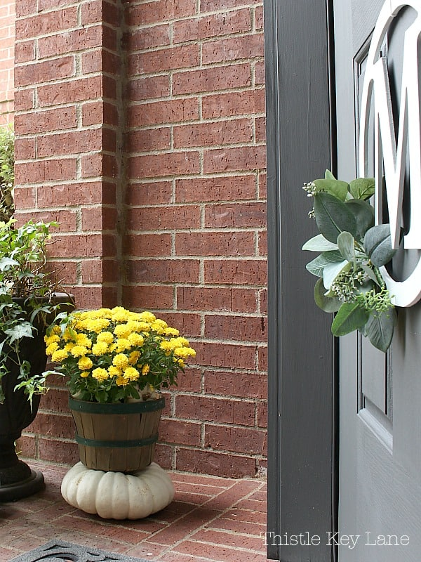 Eucalyptus wreath on the front door with mums and pumpkins on the porch.