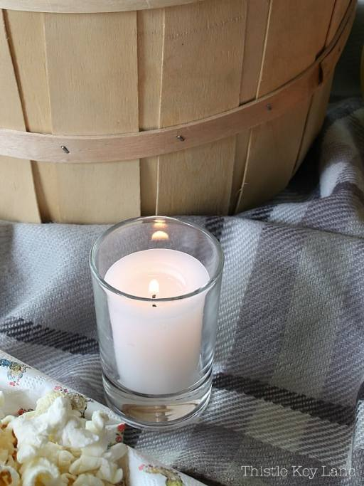 White candle nestled between a bushel basket and popcorn.