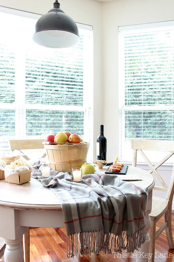 Tablescape with a bushel basket of apples, candles, snacks and a plaid throw.
