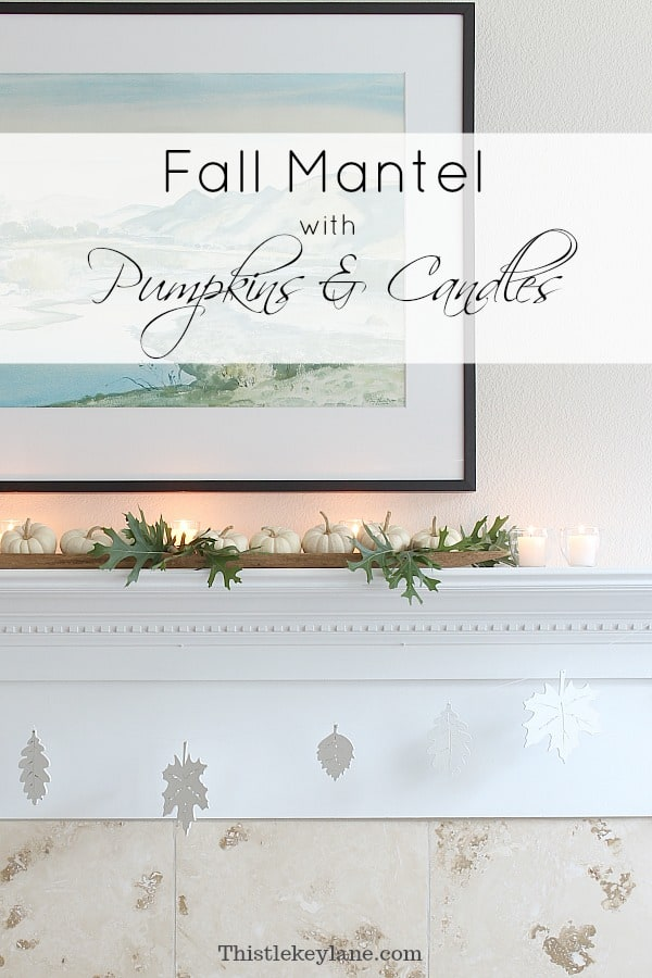 Fall mantel decorated with oak leaves, pumpkins and candles.