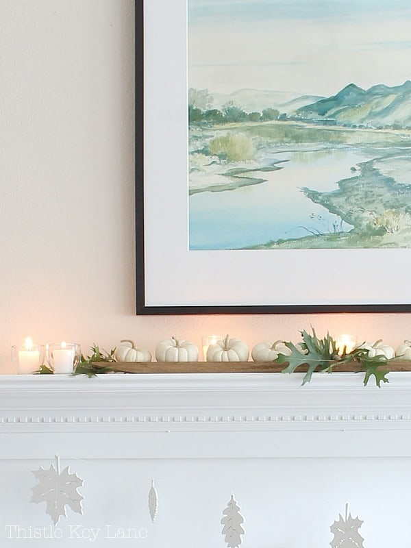White mantel decorated with white pumpkins, oak leaves and candles.