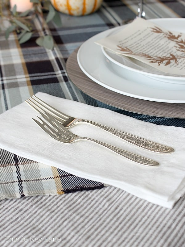 Vintage silverware on a white linen napkin.