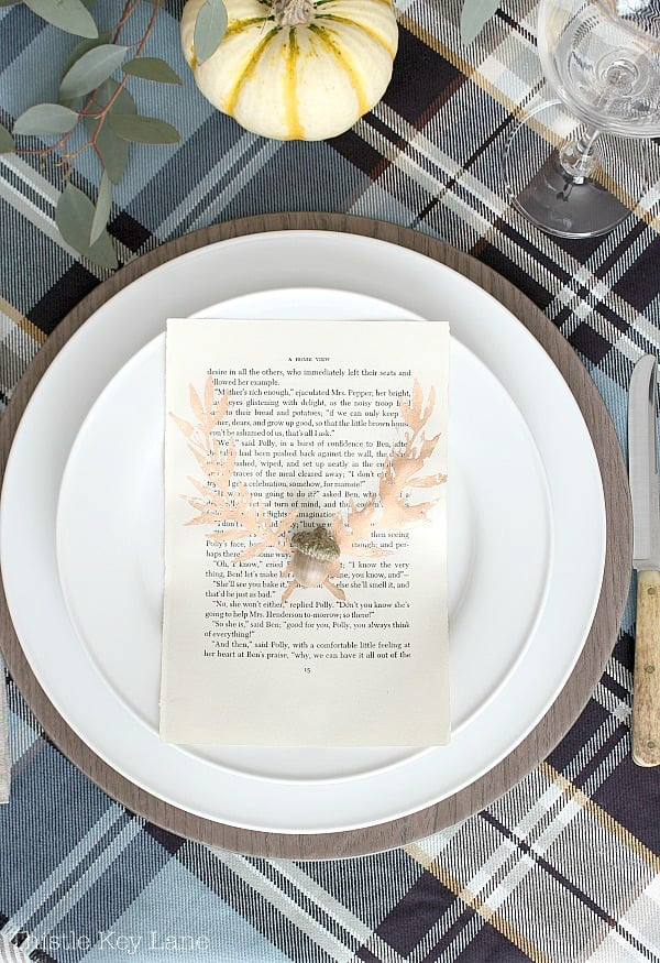 White place setting with copper laurel and plaid background.