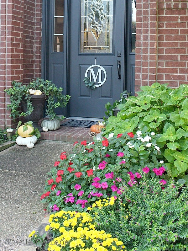 Summer flowers and pumpkins on the porch say welcome fall.