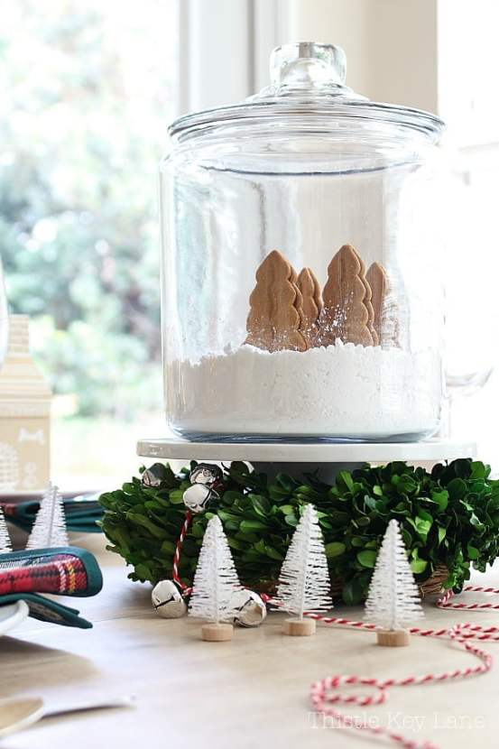 Centerpiece with boxwood, cake plate and cookie jar with snowy trees.