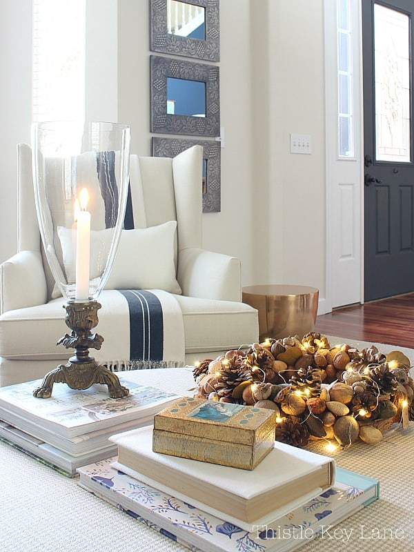 Simple setting of books, a candle and a pinecone wreath sitting on an ottoman.