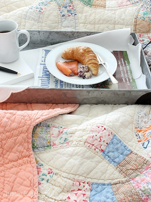 Breakfast tray on bed with a quilt.