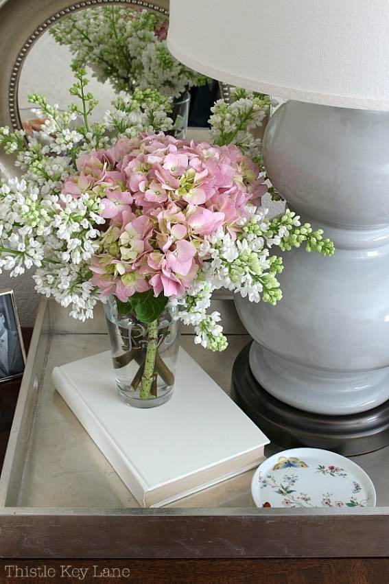 Pink hydrangea and lilacs on a tray.