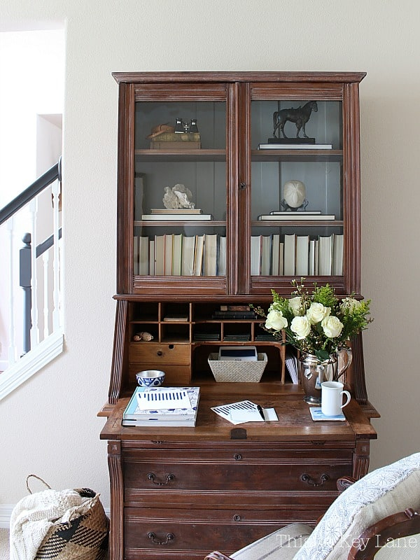 Secretary desk with books and flowers.