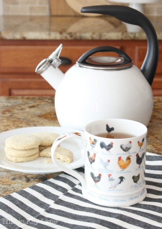 Tea mug with roosters, plate of cookies and a white tea kettle.