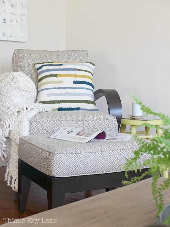 Brown and white arm chair with throw striped throw pillow.