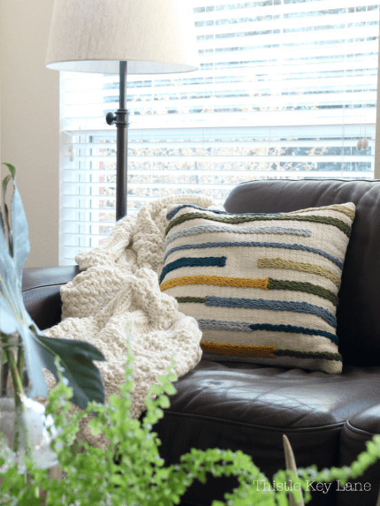 Cozy throw blanket and pillow on leather sofa.