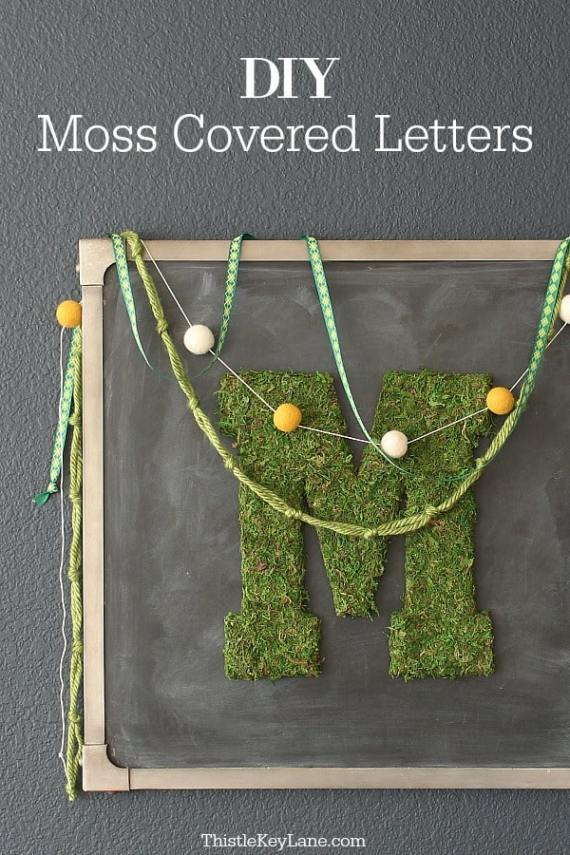 Chalkboard decorated with moss letter M and a pompom garland.