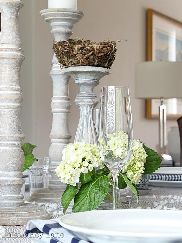 Tall wood candlesticks with birds nest and green hydrangea arrangements.