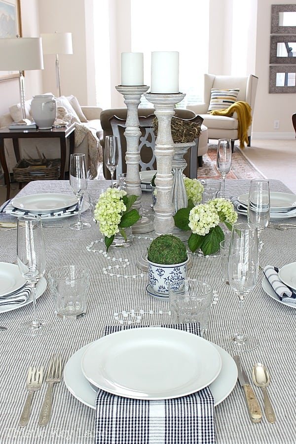 Table set with white dishes on a striped tablecloth, green hydrangeas and tall candle sticks.