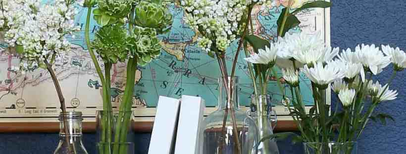 White flowers and vases on a tray with books.