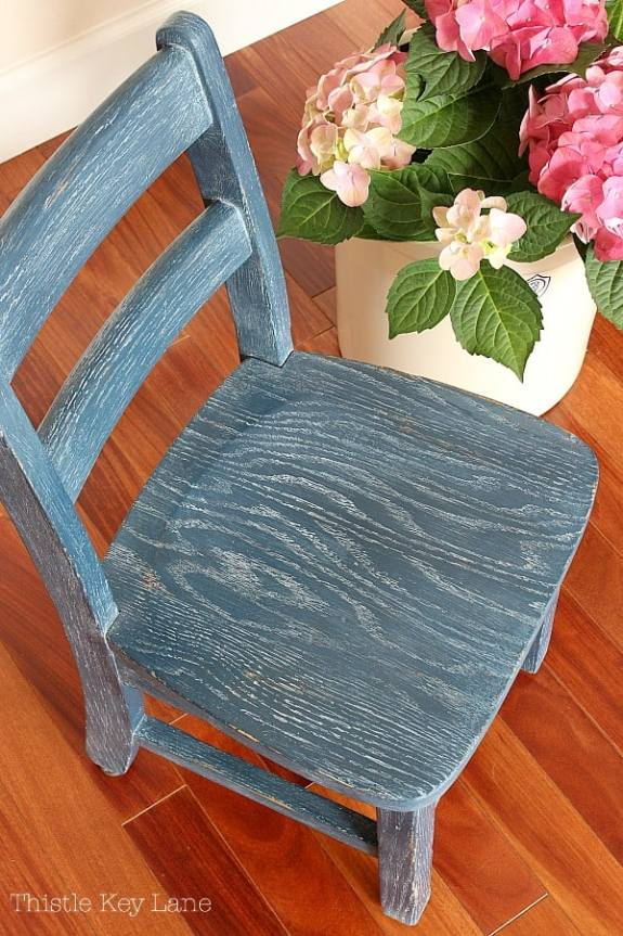 Top view of child's chair painted blue and liming wax finish.