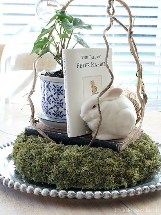 Centerpiece with white bunny, Peter Rabbit book, potted ivy sitting on top of a deer moss wreath.