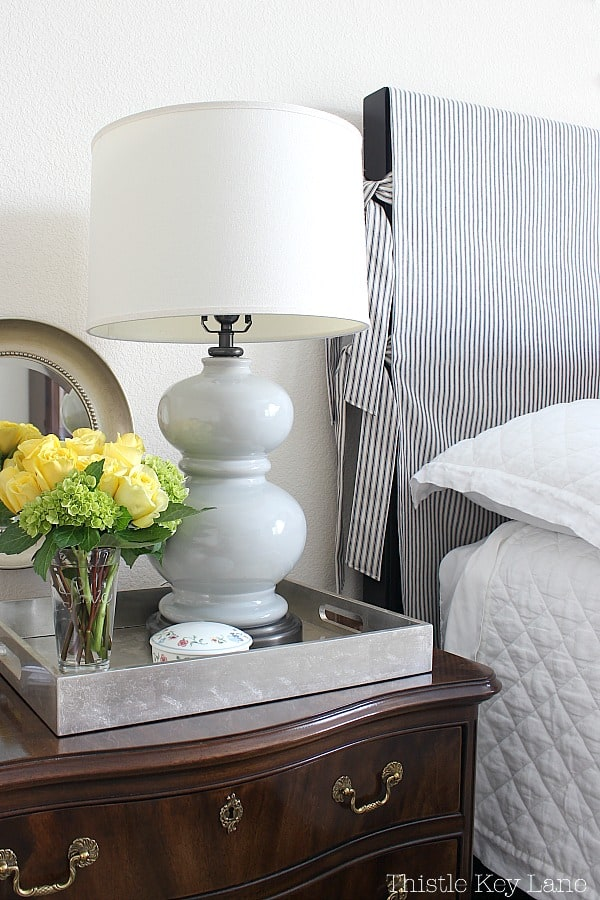 Yellow roses on the bedside table are part of the updating a bedroom with patterns and colors.