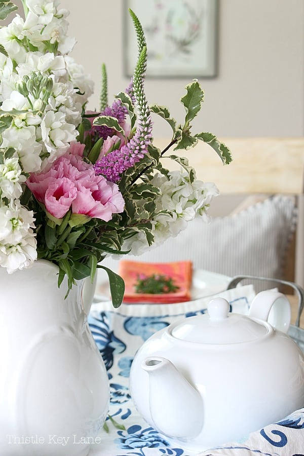 Flower arrangement and tea pot on a blue and white cloth.