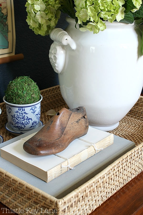 Entry table tray with mini moss topiaries and a vintage wood shoe mold.