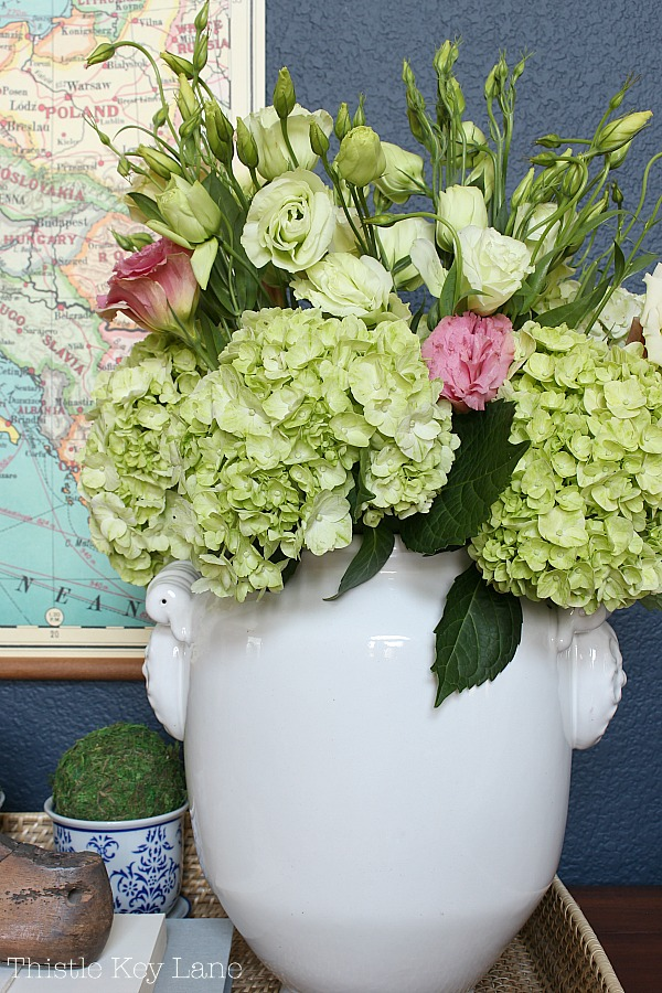 Green hydrangea in a white urn on the entry table.