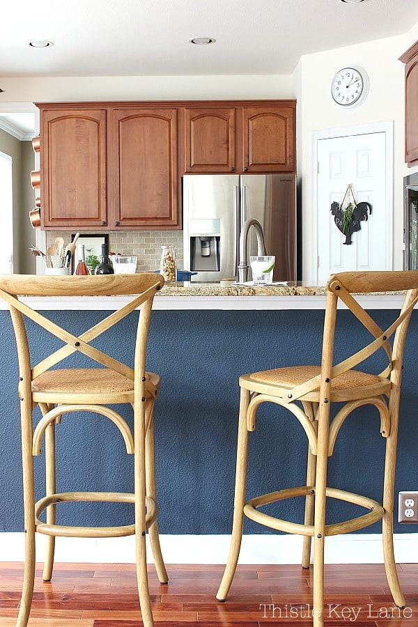 Neutral bistro bar stools with navy wall and kitchen.