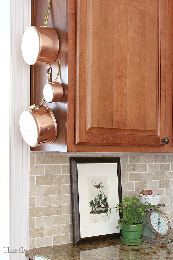 Transitioning Summer To Fall Kitchen Ideas with copper posts hanging from cabinets.
