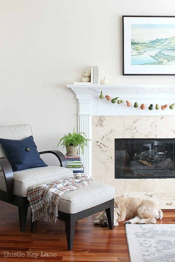 Navy and plaid accents on the chair in front of the fireplace.