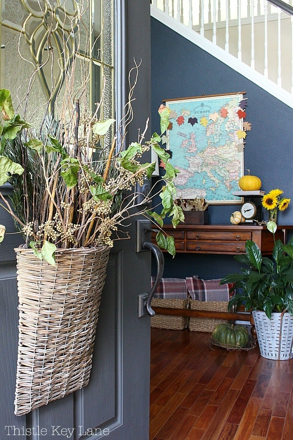 Fall Entryway With Navy And Yellow - Willow basket with dried arrangement on dark gray door.