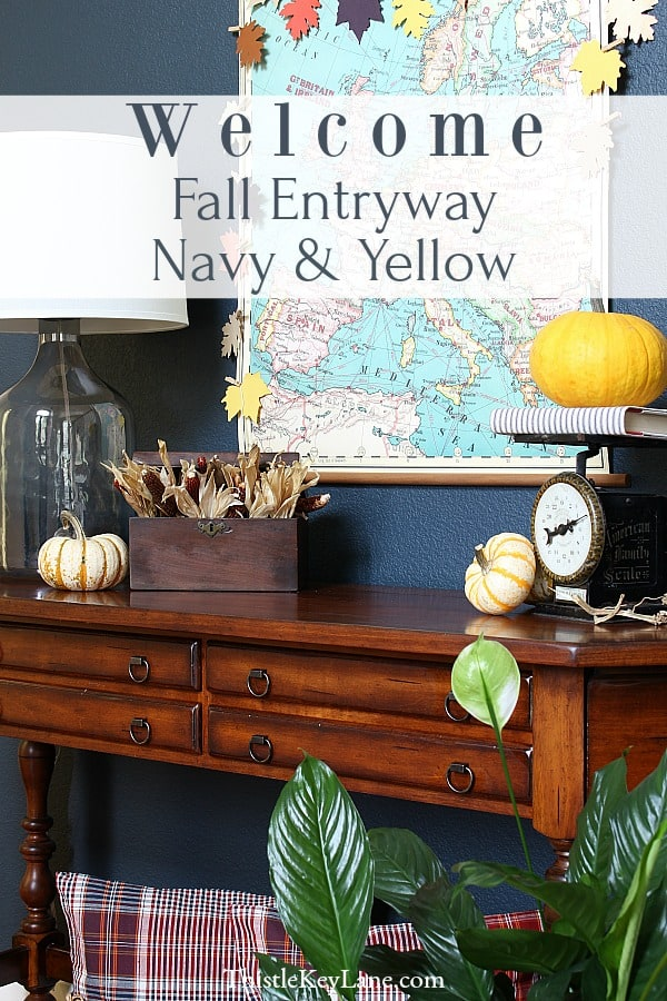 Fall Entryway With Navy And Yellow - entry table with navy wall, vintage map, garland and pumpkins.