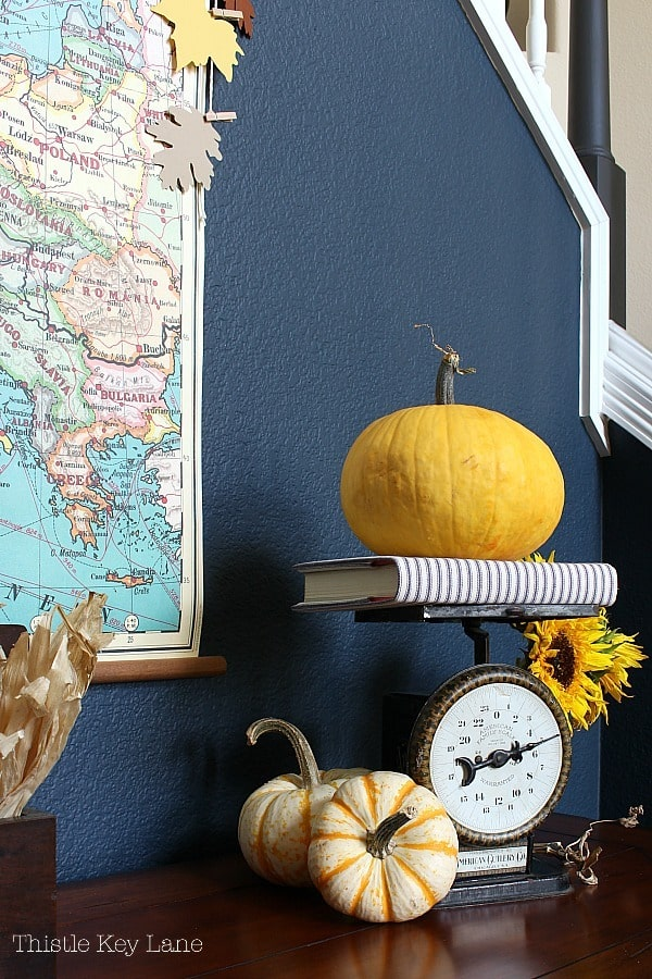 Vintage vignette with scale and pumpkins with map and navy wall.