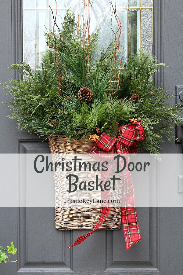 Holiday Basket Door Decoration with red plaid bow and winter greenery.