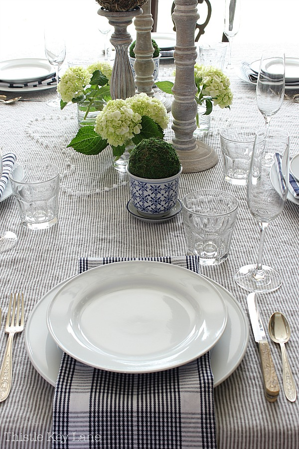 French style tablescape with linen, hydrangeas, wood candlesticks and blue ceramic topiaries.