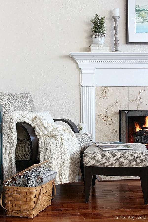 Winter Decorating Family Room Tour - Chair and ottoman with a cream knitted throw in front of the fireplace.