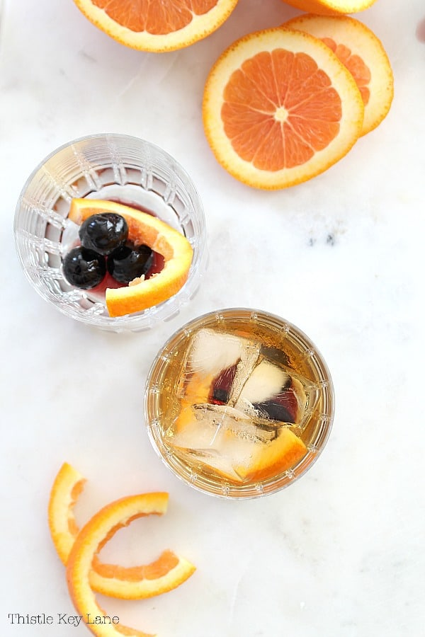 Flat lay of cocktails with cherries and orange slices.