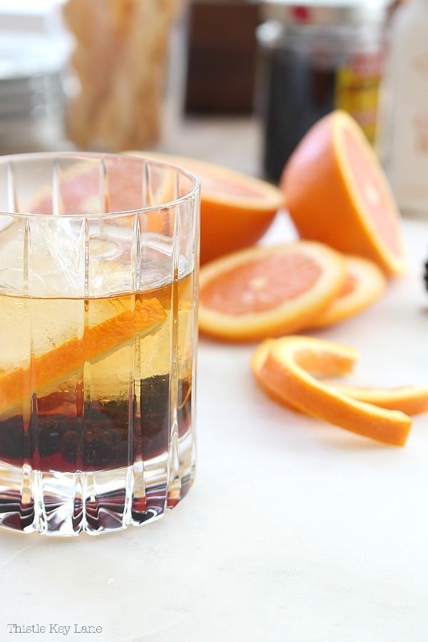 Old Fashioned cocktail with orange slices.