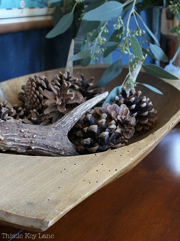 Wooden dough bowl with pine cones and antler.