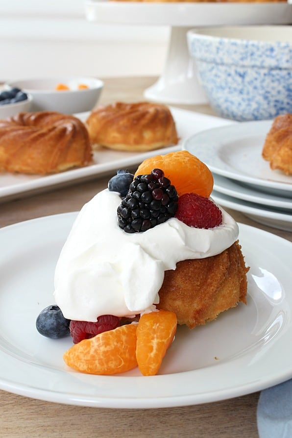 Mini Pound Cake Recipe - with cake covered in whipped cream and fruit.