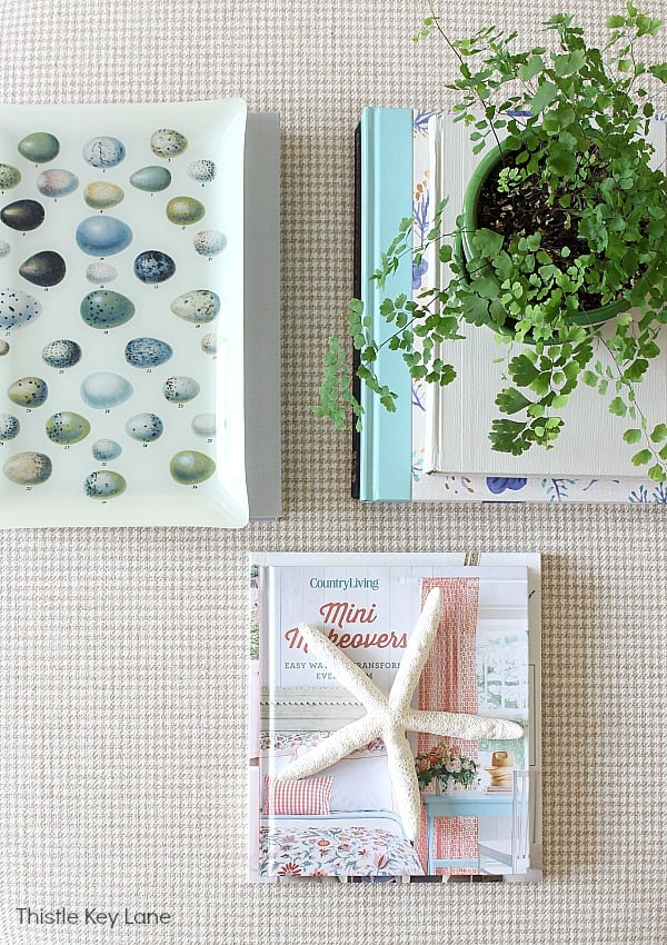 Spring Decorating Ideas For An Ottoman - flat lay of books, tray and fern.