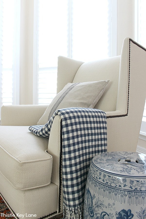 White wingback chair with blue check throw.