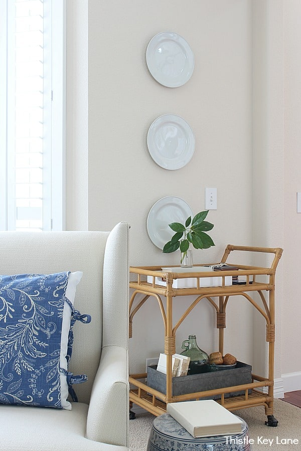 Ideas For Decorating With Plates - White plates hanging over rattan bar cart.