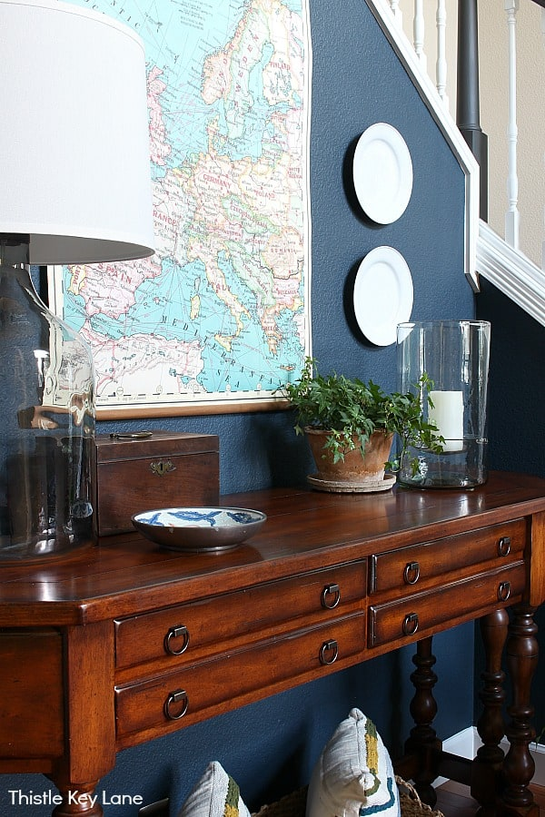 Dark wood entryway table with lamp, plant, candle, map and plates with navy wall background.