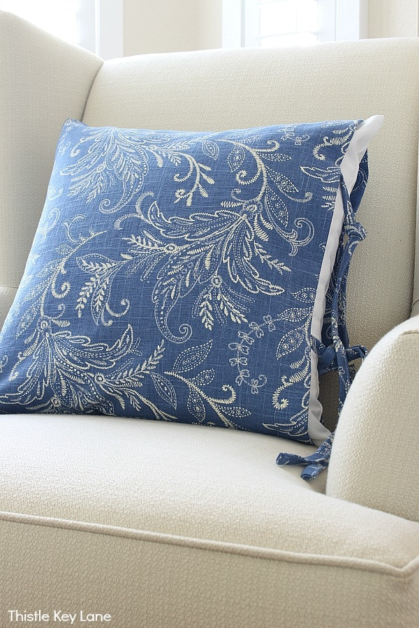 Blue and white pillow cover with knotted ties on the side.