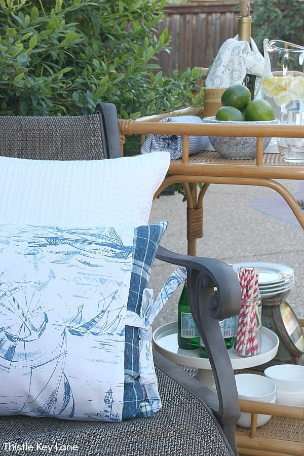 Relaxing Patio Style With Blue And White Accents - pillows on a chair with bar cart in background.