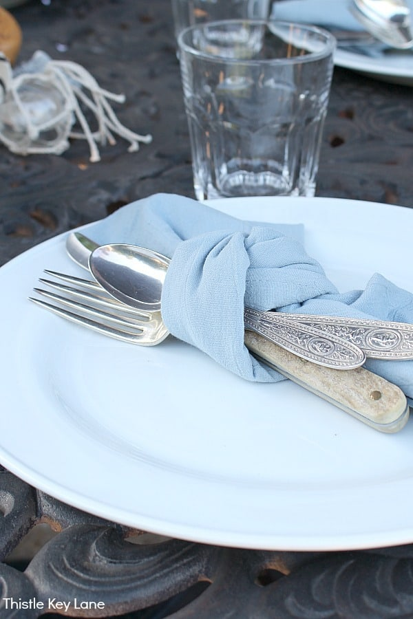 Relaxing Patio Style With Blue And White Accents - white plate with utensils tied with a blue napkin.