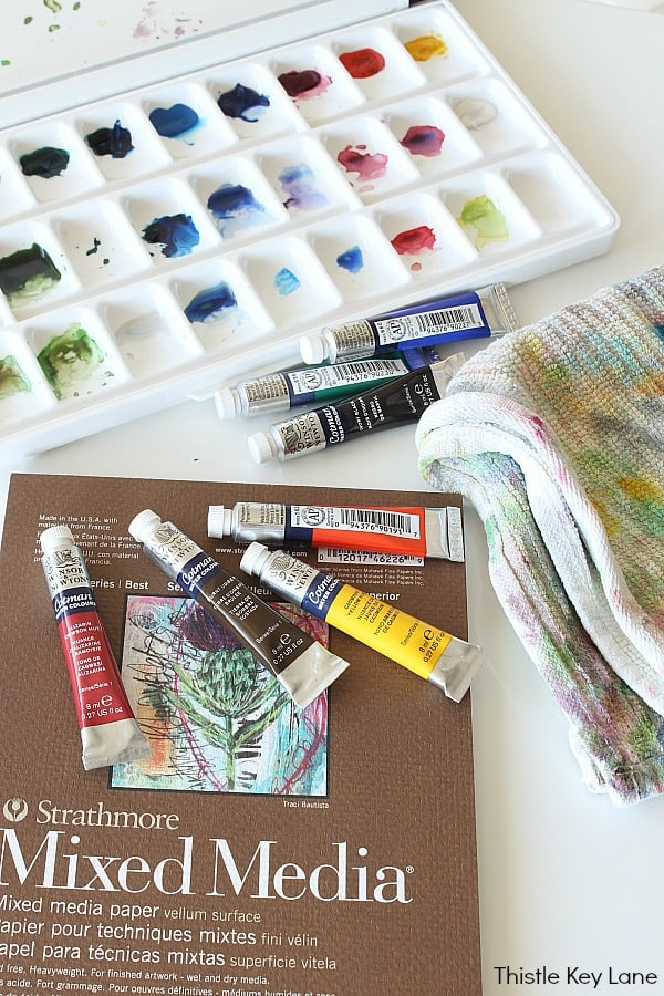 Watercolor paints in tray, with paint rag and tubes of paint.